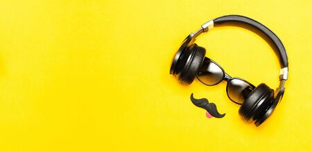 Creative party decoration concept. Black mustache, Sunglasses, headphones for music, props for photo booths carnival parties on yellow background top view flat lay. Father's day, Men's accessories.