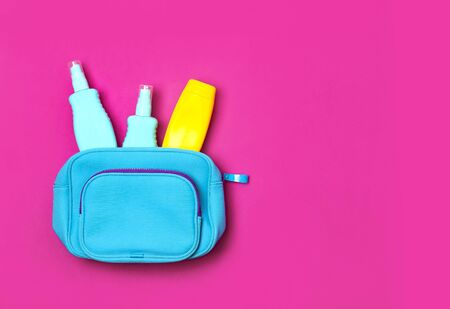 Female cosmetics bag, cosmetic products, yellow sunscreen bottle and sunblock lotion, spray on bright pink fuchsia background top view flat lay. Minimalism cosmetics style. Bright summer concept.