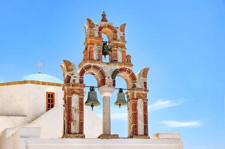 Beautiful old orthodox white church with blue dome and the old arch with bells against the blue sky, Santorini, Greece, Europe. Classic white Greek architecture, houses, churches. Travel concept.