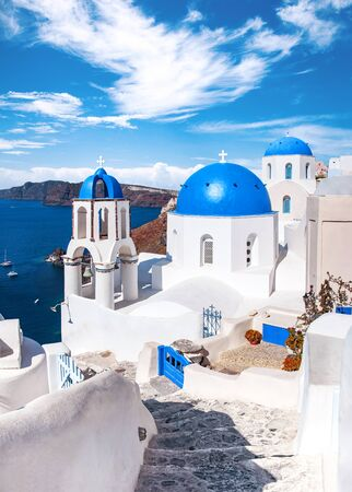 Traditional and famous houses and churches with blue domes over the Caldera, Oia, Santorini, Greece island, Aegean sea. Beautiful view of White Greek architecture. Travel, Famous travel destination.