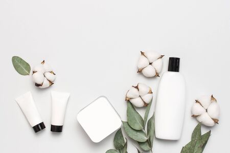 Cosmetics SPA branding mock-up. White cosmetic bottle containers with cotton flowers, eucalyptus twigs on gray background top view flat lay. Natural organic beauty product concept, Minimalism style.