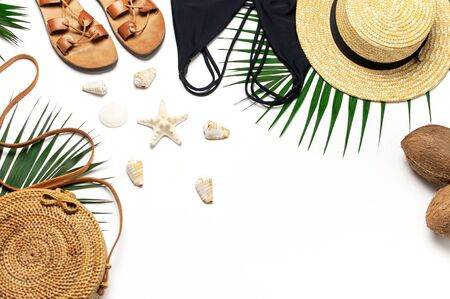 Woman's beach accessories flat lay. Round trendy rattan bag straw hat black swimsuit leather sandals tropical palm leaves coconut seashells on white background. Top view copy space. Summer backdrop.