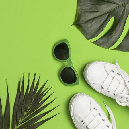 White female fashion sneakers, trendy sunglasses, tropical leaves on green background. Flat lay top view copy space. Women's shoes, accessories. Stylish white sneakers. Creative summer concept. Stock Photo