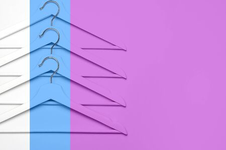 Creative fashion concept. Flat lay top view colored wooden hangers on pink blue background minimalism style pop-art. Sale discount store shopping concept, design empty hanger. Beauty feminine blog.