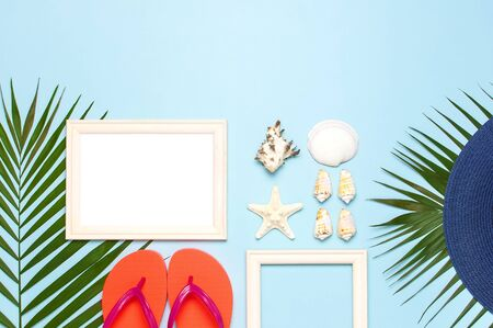 Summer fashion flat lay. Blue hat coral flip flops tropical palm leaves sunscreen white photo frame coconut seashells starfish on blue background. Top view copy space. Creative vacation background.