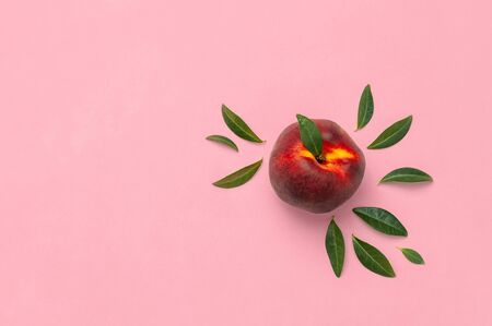 Flat lay composition with peaches. Ripe juicy peaches with green leaves on pink background. Flat lay, top view, copy space.