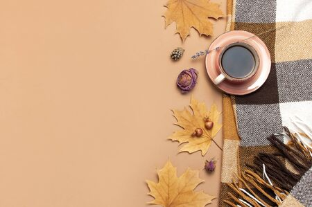 Autumn Flat lay composition. Cup of tea, checkered plaid, autumn dry leaves, roses flowers, orange circle cones decorative pomegranate cinnamon sticks on brown beige background top view. Fall concept.