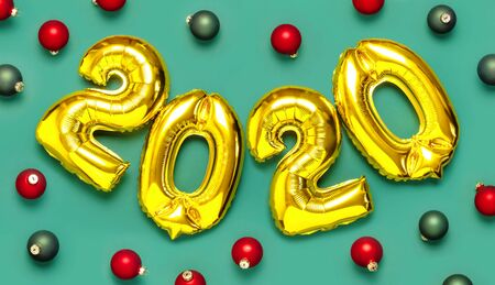 2020 inflatable golden numbers with red and green christmas balls on green background. New year winter decoration, holiday symbol, party item. Merry Christmas greeting card. Happy New Year. Flat lay.