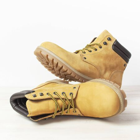 Close-up Yellow men's work boots from natural nubuck leather on wooden white background. Trendy casual footwear youth style. Concept of advertising autumn winter shoes sale shop.
