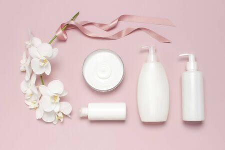 Beauty Spa concept. Opened container with cream, cosmetic bottle containers, white Phalaenopsis orchid flowers on pink background Flat lay top view. Herbal dermatology cosmetic hygienic cream.