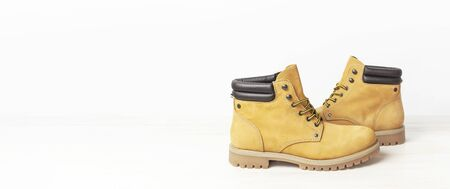Yellow mens work boots from natural nubuck leather on wooden white background. Trendy casual footwear, youth style. Concept of advertising autumn winter shoes, sale, shop. Фото со стока