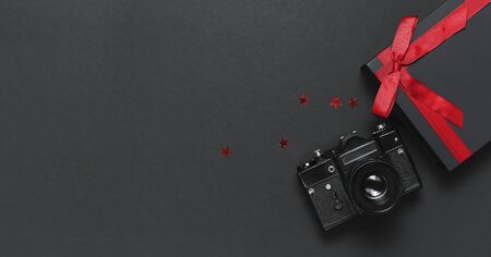 Old retro vintage camera, Black gift box with red ribbon, confetti on black background top view flat lay with copy space. Concept for the photographer, old photographic equipment, minimalistic style.