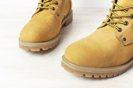 Close-up Yellow mens work boots from natural nubuck leather on wooden white background. Trendy casual footwear youth style. Concept of advertising autumn winter shoes sale shop.
