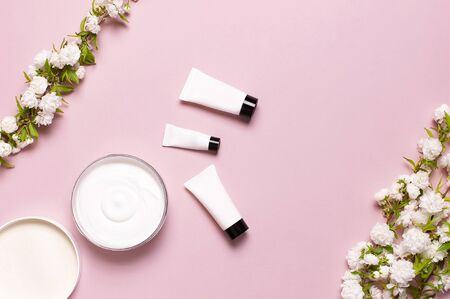 Beauty Spa concept. Opened plastic container with cream, cosmetic bottle containers, spring White flowers on pink background Flat lay top view. Herbal dermatology cosmetic hygienic cream organic.