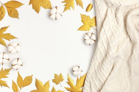 Flat lay autumn composition. Knitted woolen light beige sweater or plaid, golden dry leaves, cotton flowers on white background top view copy space. Autumn, fall concept.