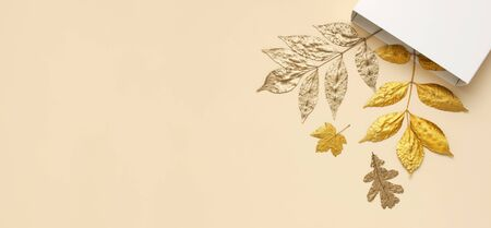 Flat lay creative autumn composition. White Gift Paper package and Golden leaves on beige background top view copy space. Fall concept. Autumn background. Minimal concept idea, floral design. Stock fotó