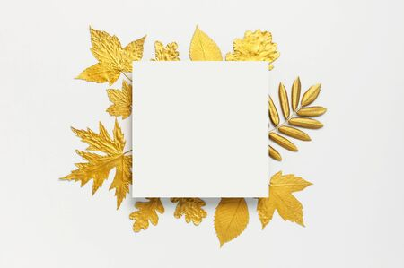 Flat lay creative autumn composition. Paper blank and Golden leaves on white gray background top view copy space. Fall concept. Autumn background. Minimal concept idea, floral design.