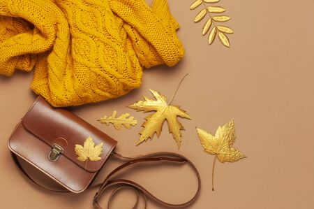 Brown leather women bag, orange knitted sweater, golden autumn leaf on brown background top view flat lay copy space. Fashionable women's accessories. Autumn Fashion Concept. Stylish Lady Clothes.