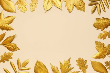 Flat lay creative autumn composition. Frame from Golden leaves on beige background top view copy space. Fall concept. Autumn background. Minimal concept idea, floral design. Reklamní fotografie - 129262991
