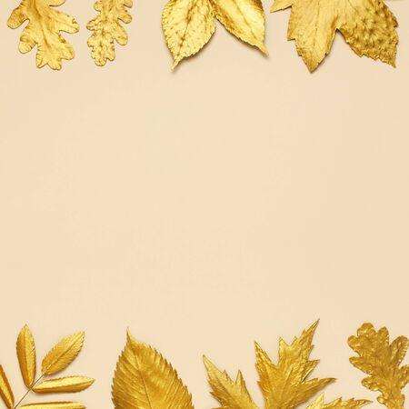 Flat lay creative autumn composition. Frame from Golden leaves on beige background top view copy space. Fall concept. Autumn background. Minimal concept idea, floral design. Square format. Reklamní fotografie