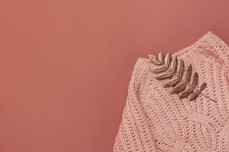 Flat lay autumn composition. Knitted woolen pink female sweater or plaid, golden dry leaves on burgundy brown background top view copy space. Fall concept. Fashion color, cozy autumn thing, clothes.