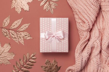Flat lay autumn composition. Knitted woolen pink female sweater or plaid, pink gift with ribbon, golden dry leaves on burgundy brown background top view copy space. Autumn gift, fall concept.