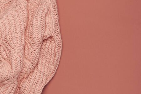 Flat lay autumn composition. Knitted woolen pink female sweater or plaid on burgundy brown background top view copy space. Fall concept. Fashion color, fashionable cozy autumn thing, clothes.