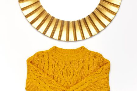 Fashionable vintage modern golden frame, knitted orange sweater isolated on white background. Photo frame, mirror frame, baguette, stylish interior item. Autumn, fall concept.