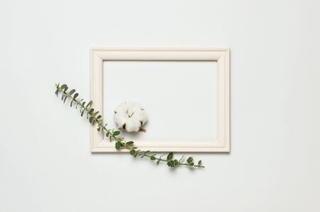 White wooden photo frame and spring green twigs of plants on gray background. Flat lay top view copy space. Stylish minimal composition, artwork mockup, picture frame, home decoration. Imagens