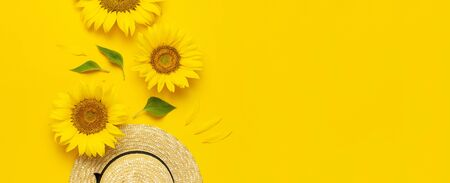 Beautiful fresh sunflowers, straw hat on bright yellow background. Flat lay top view copy space. Autumn or summer Concept, harvest time, agriculture. Sunflower natural background. Flower card. Stock Photo