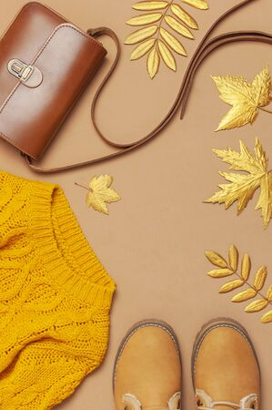 Brown leather women bag, orange knitted sweater, warm boots, golden autumn leaf on brown background top view flat lay. Fashionable womens accessories. Autumn Fashion Concept. Stylish Lady Clothes.