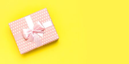 Gift or present box with beautiful festive ribbon on yellow background top view. Flat lay composition for celebration, holiday, birthday, Valentines Day, March 8, mother day, wedding. Congratulation.