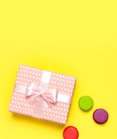 Gift or present box, macaroon on yellow background top view. Creative Flat lay composition for celebration, holiday, birthday, Valentines Day, March 8, mother day, wedding.