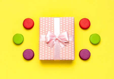 Gift or present box, or macaroon on yellow background top view. Creative Flat lay composition for celebration, holiday, birthday, Valentines Day, March 8, mother day, wedding.