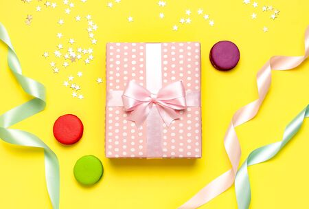 Gift or present box, beautiful festive ribbon, macaroon, confetti on yellow background top view. Flat lay composition for celebration, birthday, Valentines Day, March 8, mother day.