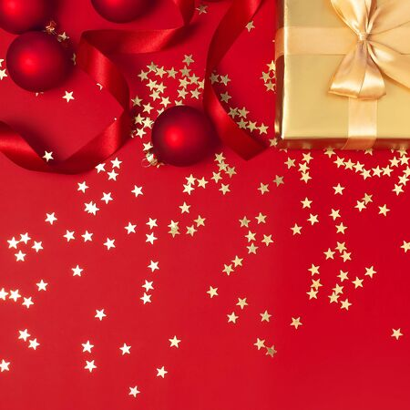 New Year Christmas golden presents with ribbon, Christmas balls, gold confetti stars on red background top view. Flat lay Xmas holiday 2020 celebration. Gift boxes greeting card Festive decorations. Foto de archivo