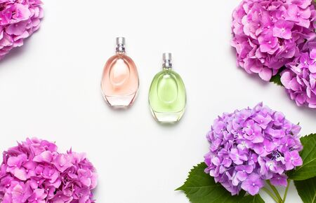 Perfume bottles and pink hydrangea flowers on light gray background top view Flat lay copy space. Perfumery, cosmetics, female accessories, fragrance collection. Delicate Perfume Bottle.