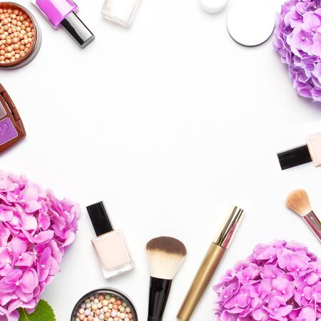 Set of decorative cosmetics mascara powder lipstick eyeshadow blush makeup brush pink hydrangea flowers on light background top view Flat lay copy space. Beauty blogger concept. Fashion background.