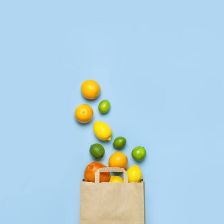 Creative background with tropical fruits. Orange, lemon, lime, grapefruit drop out of paper bag on blue background. Flat lay top view copy space. Food concept, vitamin C, disease prevention, flu. 版權商用圖片