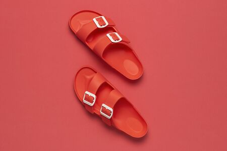 Fashionable beach coral birkenstock on bright coral background. Flat lay, top view, copy space. Creative beach concept, stylish summer shoes, vacation, travel. Coral color. Summer background. 免版税图像