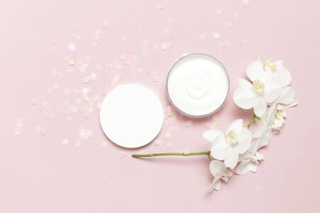 Beauty Spa concept. Opened plastic container with cream and White Phalaenopsis orchid flowers on pink background Flat lay top view. Herbal dermatology cosmetic hygienic cream, organic cosmetic Natural. 스톡 콘텐츠