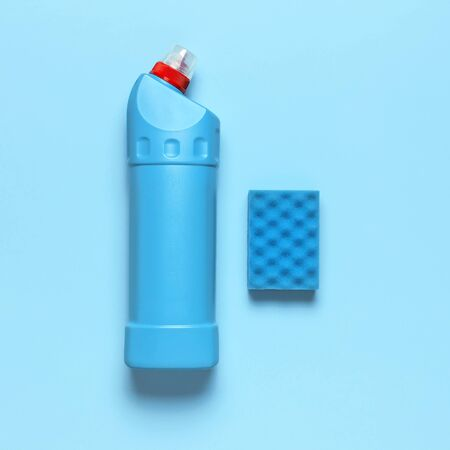 Blue plastic bottle for liquid detergent, cleaning agent, bleach, antibacterial gel and washing sponge on blue background. House cleaning concept. Flat lay top view. Cleaning accessories.