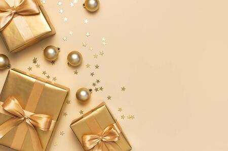 Merry Christmas and Happy Holidays greeting card. Beautiful golden gift with balls and confetti stars on gold background top view Flat lay. New Year presents Festive decorations 2020 celebration.