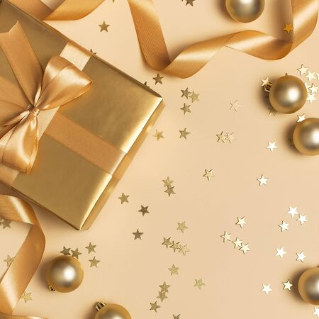 Merry Christmas and Happy Holidays greeting card. Beautiful golden gift balls ribbons confetti stars on gold background top view Flat lay. New Year presents Festive decorations 2020 celebration.