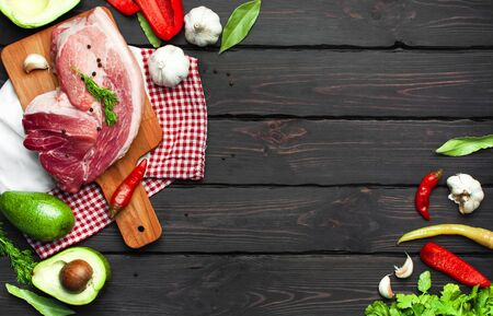 Big fresh piece of meat on cutting board with ingredients for cooking pepper garlic avocado dill parsley on dark wooden background top view. Raw steak from pork or beef. Cooking concept, healthy food. Stock Photo