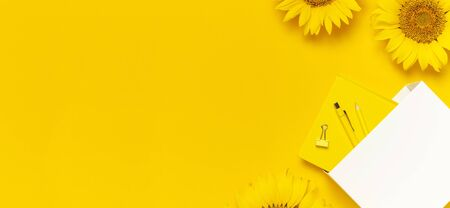 Top view flat lay of workspace desk styled design with sunflowers, white paper bag pencils pen notebook diary paper clips on yellow background. Autumn or summer Concept. Sunflower natural background.