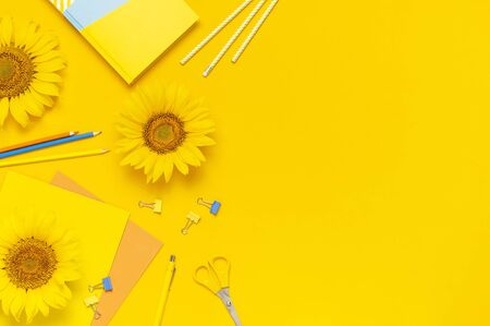 Top view flat lay of workspace desk styled design with sunflowers notebook diary pencils pen scissors on yellow background. Autumn or summer Concept. Sunflower natural background. Stationery.