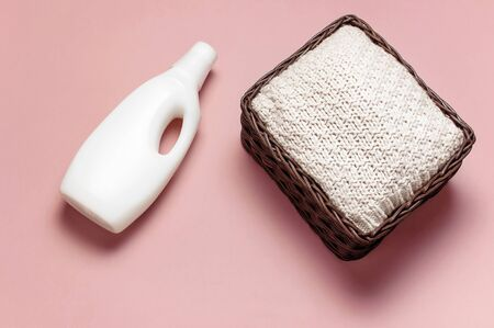 Eco washing concept. White plastic packaging of laundry detergent, liquid powder, washing conditioner, knitted sweater, rattan wicker basket on pink background. Flat lay top view. Bio organic product.