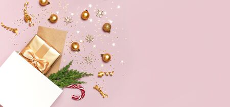 Beautiful golden gift white paper bag confetti stars Christmas balls on pink background top view Flat lay. New Year presents Festive decorations 2020 celebration. Merry Christmas Happy Holidays card.