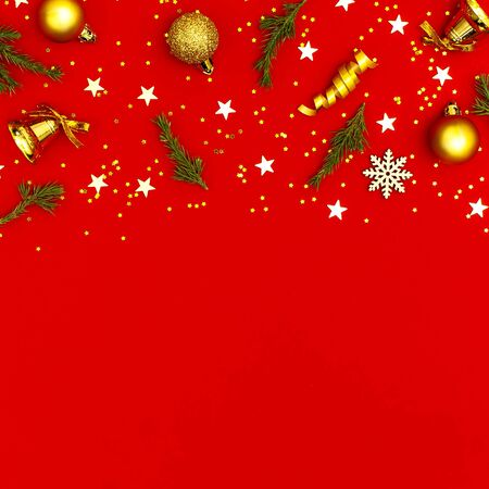 New Year Christmas composition. Holiday decorations gold Christmas balls fir branches confetti snowflakes bell on red background. Flat lay top view copy space. Winter New Year 2020 Xmas celebration.